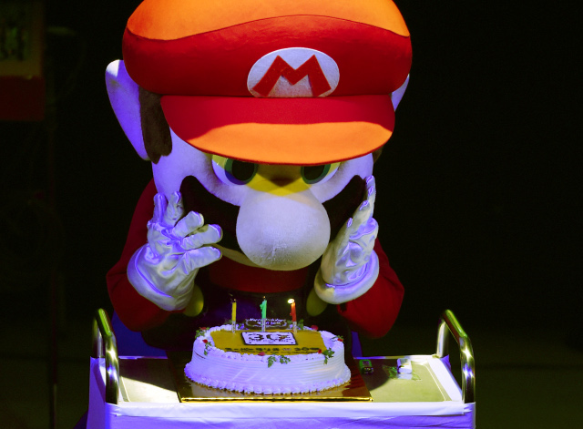 """Super Mario"" blows out the candles on a cake during celebrations and a live performance of the most well-known Mario music to mark the game's 30th anniversary in Tokyo on September 13, 2015. Nintendo celebrated the 30th anniversary of Super Mario, one of the best-known characters in video game history, at the event in Tokyo where artists played his theme music to fans dressed up as the hyperactive plumber. AFP PHOTO / TOSHIFUMI KITAMURA"